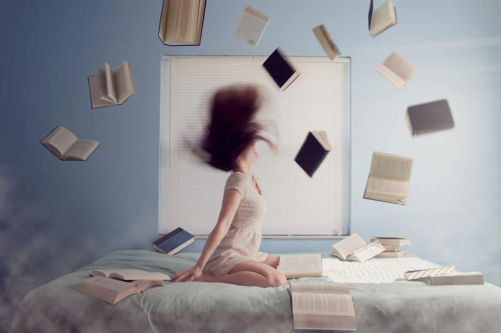 side gig - woman on bed with books flying in the air